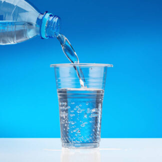 Sparkling water flows from bottle into glass. Blue background, copy space.