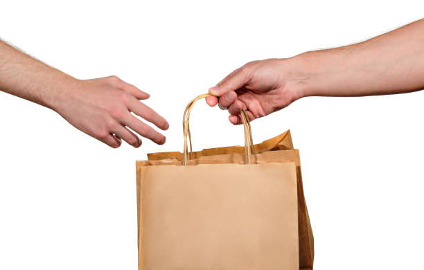Grocery store delivery service employee gives a paper bag to a customer