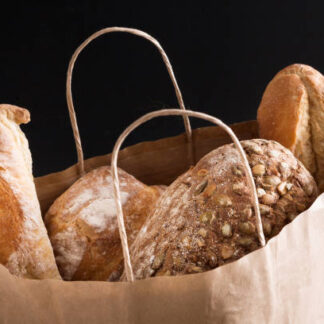 Bread assortment in paper bag isolated at black background. Shopping at bakery