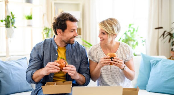 Front view of happy couple sitting on sofa indoors at home, eating hamburgers.