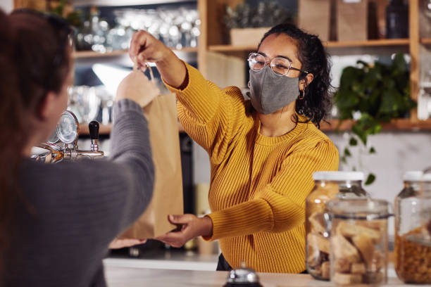 Shot of a woman wearing a mask while serving a customer in a cafe