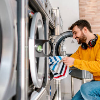 The young man does the laundry, washing himself weekly in the laundry.